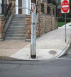 A photograph shows a misplaced pole in the middle of a curb-cut.